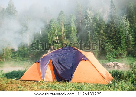 tourism, travel, tourism, tourism and the concept of active people's they, creating a tent in the open air. to collect a tent in nature. Camping and tent under a pine forest at sunset. #1126139225