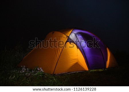 tourism, travel, tourism, tourism and the concept of active people's they, creating a tent in the open air. to collect a tent in nature. Camping and tent under a pine forest at sunset. #1126139228
