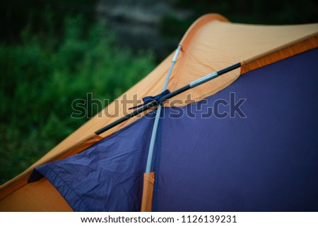 tourism, travel, tourism, tourism and the concept of active people's they, creating a tent in the open air. to collect a tent in nature. Camping and tent under a pine forest at sunset. #1126139231