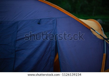 tourism, travel, tourism, tourism and the concept of active people's they, creating a tent in the open air. to collect a tent in nature. Camping and tent under a pine forest at sunset. #1126139234
