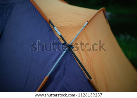 tourism, travel, tourism, tourism and the concept of active people's they, creating a tent in the open air. to collect a tent in nature. Camping and tent under a pine forest at sunset. #1126139237