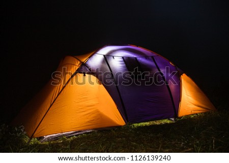 tourism, travel, tourism, tourism and the concept of active people's they, creating a tent in the open air. to collect a tent in nature. Camping and tent under a pine forest at sunset. #1126139240