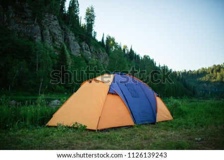 tourism, travel, tourism, tourism and the concept of active people's they, creating a tent in the open air. to collect a tent in nature. Camping and tent under a pine forest at sunset. #1126139243