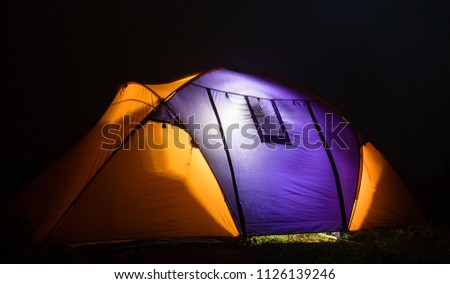 tourism, travel, tourism, tourism and the concept of active people's they, creating a tent in the open air. to collect a tent in nature. Camping and tent under a pine forest at sunset. #1126139246