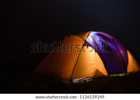 tourism, travel, tourism, tourism and the concept of active people's they, creating a tent in the open air. to collect a tent in nature. Camping and tent under a pine forest at sunset. #1126139249