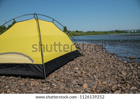 tourism, travel, tourism, tourism and the concept of active people's they, creating a tent in the open air. to collect a tent in nature. Camping and tent under a pine forest at sunset. #1126139252