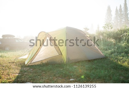 tourism, travel, tourism, tourism and the concept of active people's they, creating a tent in the open air. to collect a tent in nature. Camping and tent under a pine forest at sunset. #1126139255