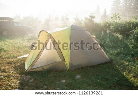 tourism, travel, tourism, tourism and the concept of active people's they, creating a tent in the open air. to collect a tent in nature. Camping and tent under a pine forest at sunset. #1126139261