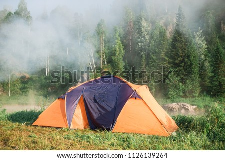 tourism, travel, tourism, tourism and the concept of active people's they, creating a tent in the open air. to collect a tent in nature. Camping and tent under a pine forest at sunset. #1126139264