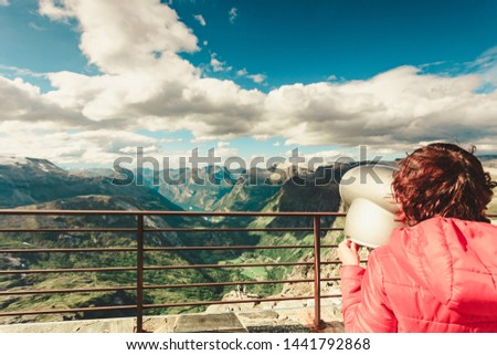 Tourism vacation and travel. Female looking through sightseeing binoculars tourist telescope, overlooking Geirangerfjord and mountains landscape from Dalsnibba viewpoint, Norway #1441792868