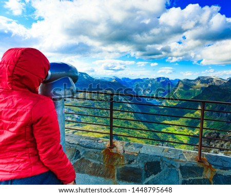 Tourism vacation and travel. Female looking through sightseeing binoculars tourist telescope, overlooking Geirangerfjord and mountains landscape from Dalsnibba viewpoint, Norway #1448795648