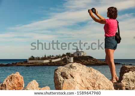 Photo of  Tourism vacation and travel. Woman tourist on sea shore taking travel photo with camera, Agios Fokas near Monemvasia, Laconia region Peloponnese.