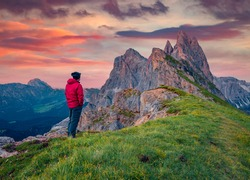 Tourist admires the fantastic sunrise with Furchetta peak on background. Gorgeous summer scene of Funes Valley. Great evening in Puez Odle National Park, Dolomiti Alps, South Tyrol, Italy, Europe.