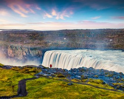 Tourist admiring view of falling water of the most powerful waterfall in Europe - Dettifoss. Colorful summer sunrise in Jokulsargljufur National Park, Iceland. Artistic style post processed photo.
