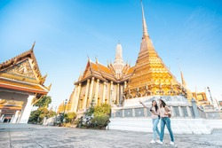 Tourist Asian women friends walking and enjoy sightseeing while travel in temple of the emerald buddha, Wat Phra Kaew, popular tourist place in Bangkok, Thailand