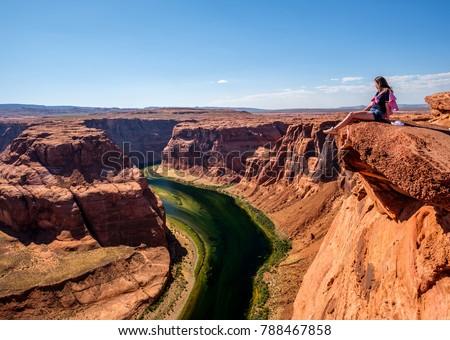 Tourist at Horseshoe Bend on Colorado River in Glen Canyon, Arizona, USA