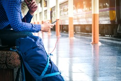 Tourist backpacker using mobile phone to travel at train station