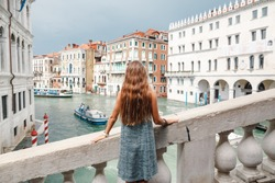 Tourist beautiful girl standing back on a bridge in Venice, Italy.View on Grand canal with woman traveler in hat on Academia bridge in Venice. Back view with copy space