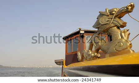 Tourist boat at the West Lake (Xihu)  near Hangzhou in China. At the background the city of Hangzhou.  At the right a traditional golden dragon