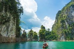 Tourist boat exploring epic limestone cliffs in huge lake in Khao Sok National Park, Chiew lan lake, Thailand.
