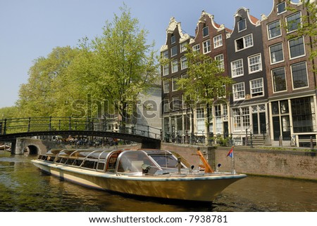 Tourist boat in an Amsterdam canal surrounded with typical Dutch old houses.