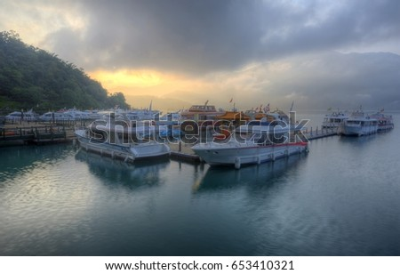 Tourist boats moored to the docks during partial solar eclipse at Shuishe Pier of Sun-Moon Lake in Nantou, Taiwan, with golden sun light shining through moody cloudy sky & reflecting on peaceful water #653410321