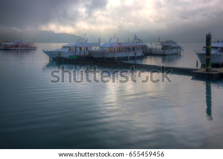 Tourist boats moored to the docks during partial solar eclipse at Shuishe Pier of Sun-Moon Lake in Nantou, Taiwan, with golden sun light shining through moody cloudy sky & reflecting on peaceful water #655459456