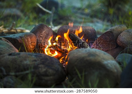 Tourist bonfire at dusk in the forest framed by stones