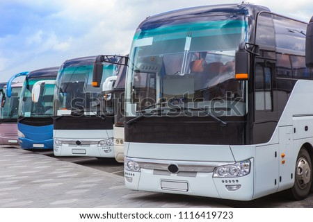 tourist buses on parking on the background of cloudy sky