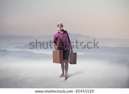 Tourist carrying some suitcases in a desert