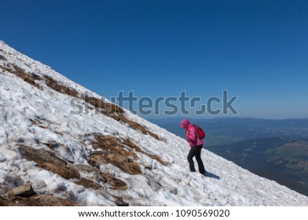 Tourist climbing on a snowy slope to the top of the mountain #1090569020