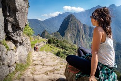 Tourist contemplating the beautiful landscape of Machu Picchu. At the bottom you can see the mountain Huayna Picchu. Archaeological site, UNESCO World Heritage