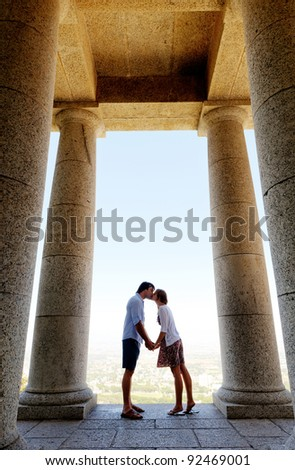 tourist coule kiss each other while visiting an old monument while traveling. a real young couple in love