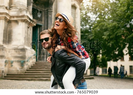Tourist Couple. Beautiful Woman And Man Having Fun, Girl Hugging Man Behind His Back On Architecture Background. Portrait Of Smiling People Spending Time Together Outdoors. High Resolution