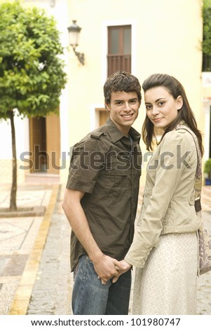 Tourist couple holding hands and smiling at camera while visiting a town on vacations.