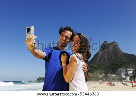 tourist couple in Rio de Janeiro taking a photo with a digital compact camera