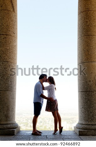 tourist couple kiss each other while visiting an old monument while traveling. a real young couple in love