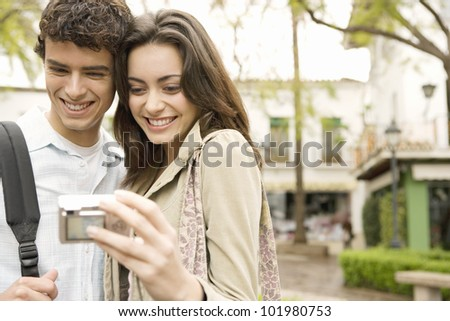 Tourist couple looking at digital photo camera's pictures and smiling together.