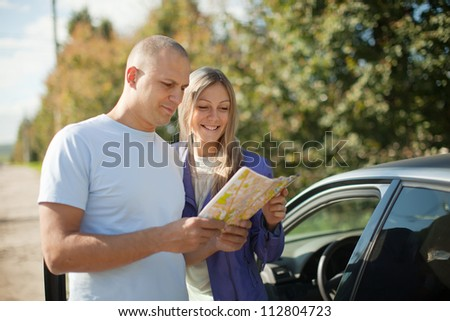 tourist couple looking at the map on the road. Focus on woman