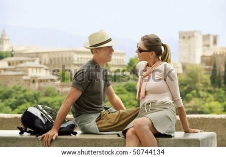 Tourist Couple Relaxing on Wall, Granada, Spain, side view