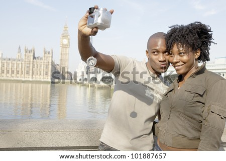 Tourist couple taking a picture of themselves while visiting Big Ben in London city. - stock photo