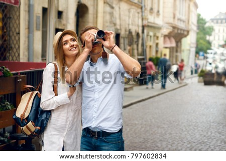 Tourist Couple Taking Photos On Camera On Street. Handsome Young Man And Beautiful Woman Traveling And Making Photos Of City Architecture On Camera. Travel And Sightseeing. High Resolution.
