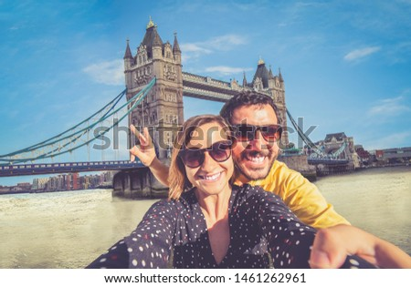 Tourist couple travelling in London taking selfie using smart phone with famous Tower Bridge on sunny day seen from Tower of London Area Landmark backgorund having fun summer in England