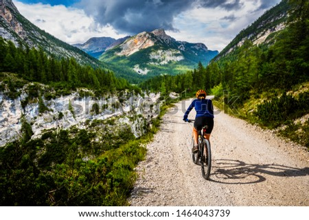 Tourist cycling in Cortina d'Ampezzo, stunning rocky mountains on the background. Woman riding MTB enduro flow trail. South Tyrol province of Italy, Dolomites. Foto stock ©