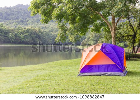 Tourist dome tent camping in forest camping site at lake side #1098862847
