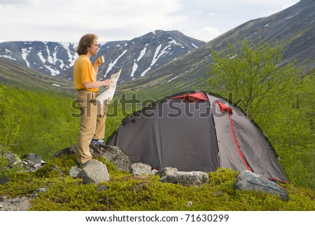 Tourist exploring a map near his tent at mountains