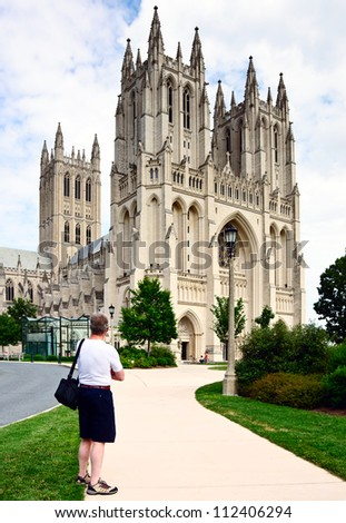 Tourist gazing at the nondenominational National Cathedral of the United States prior to earthquake damage in 2011. Important traditional venue for State ceremonies. Known for its Gothic architecture.