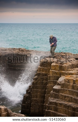Tourist getting splashed at an ancient quarry by the sea at Torre Egnatia, close to Bari, in Italy.