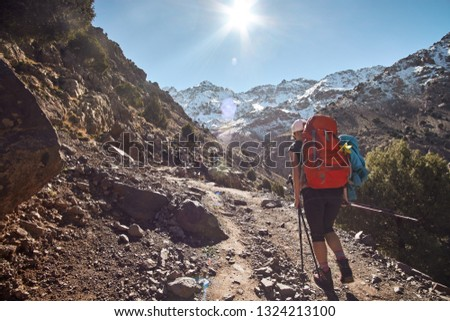 Tourist girl backpacker walking on the tourist path into the Atlas mountains in Morocco Africa #1324213100
