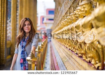 Tourist girl enjoying at Wat Phra Kaew, Temple of the Emerald Buddha, Bangkok, Thailand.